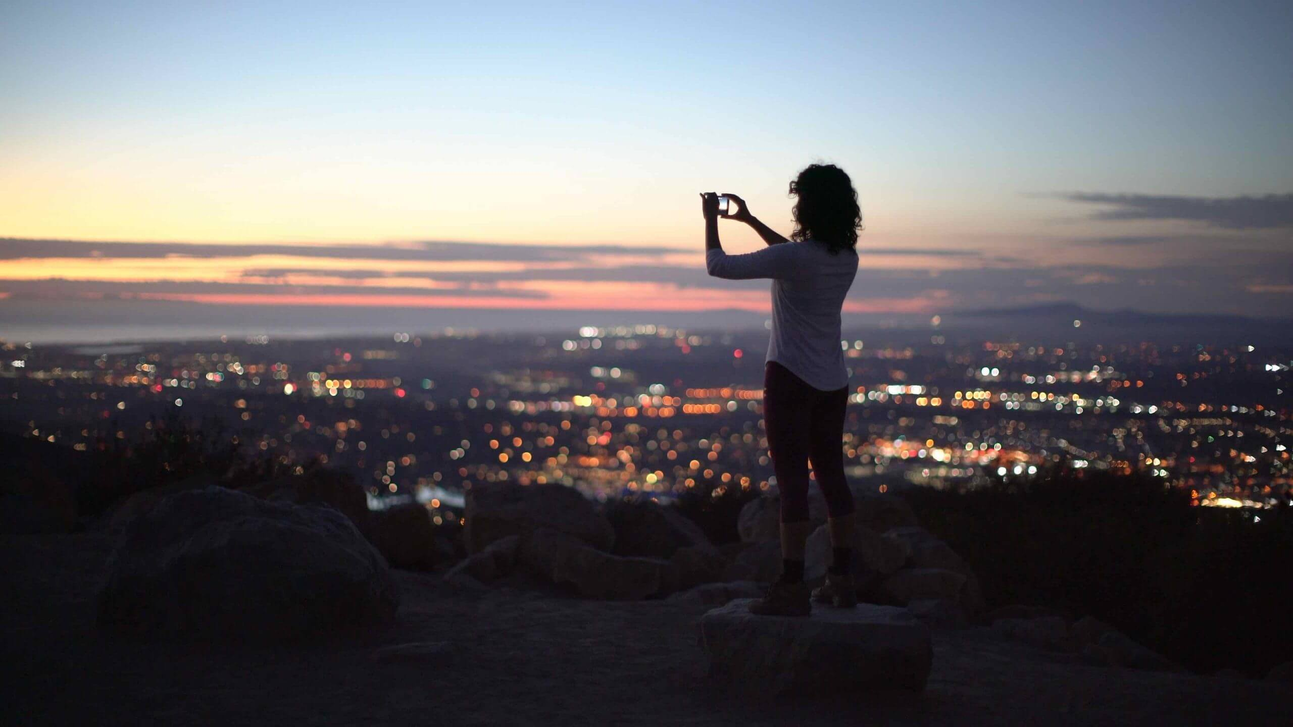 Woman recording cityscape with her mobile phone