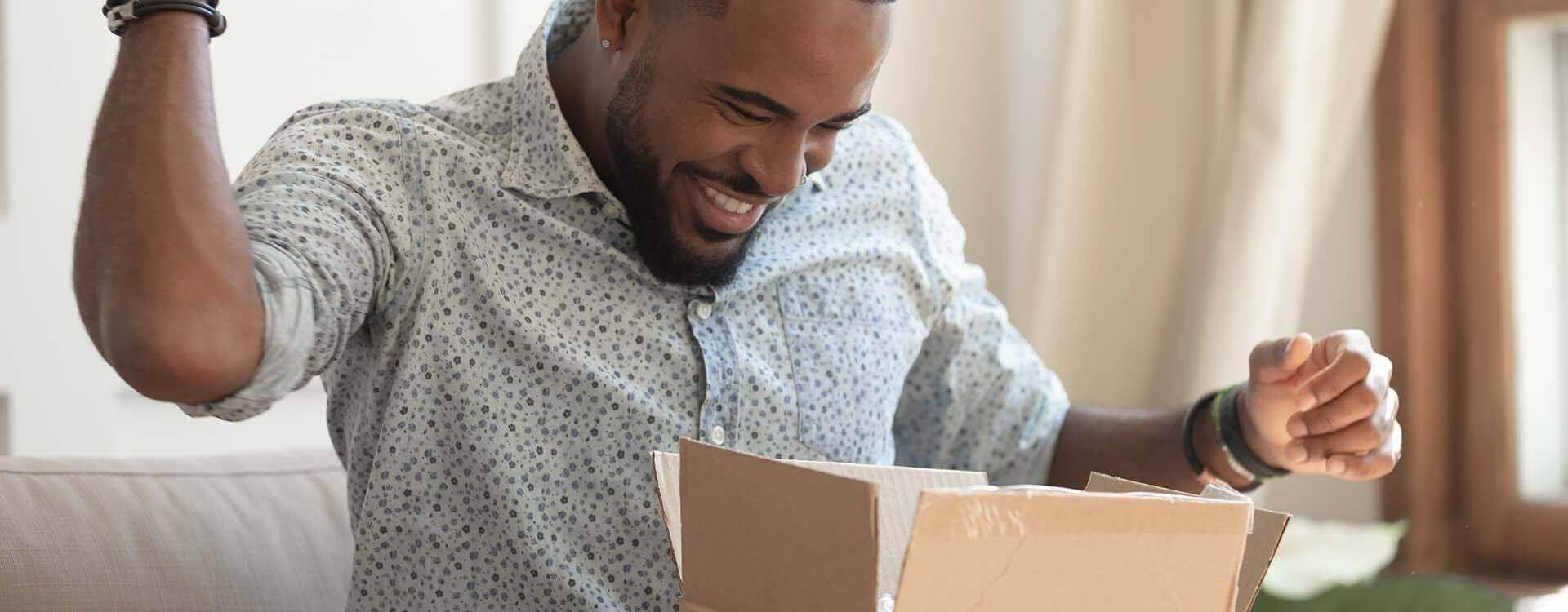 Smiling man receiving and opening parcel