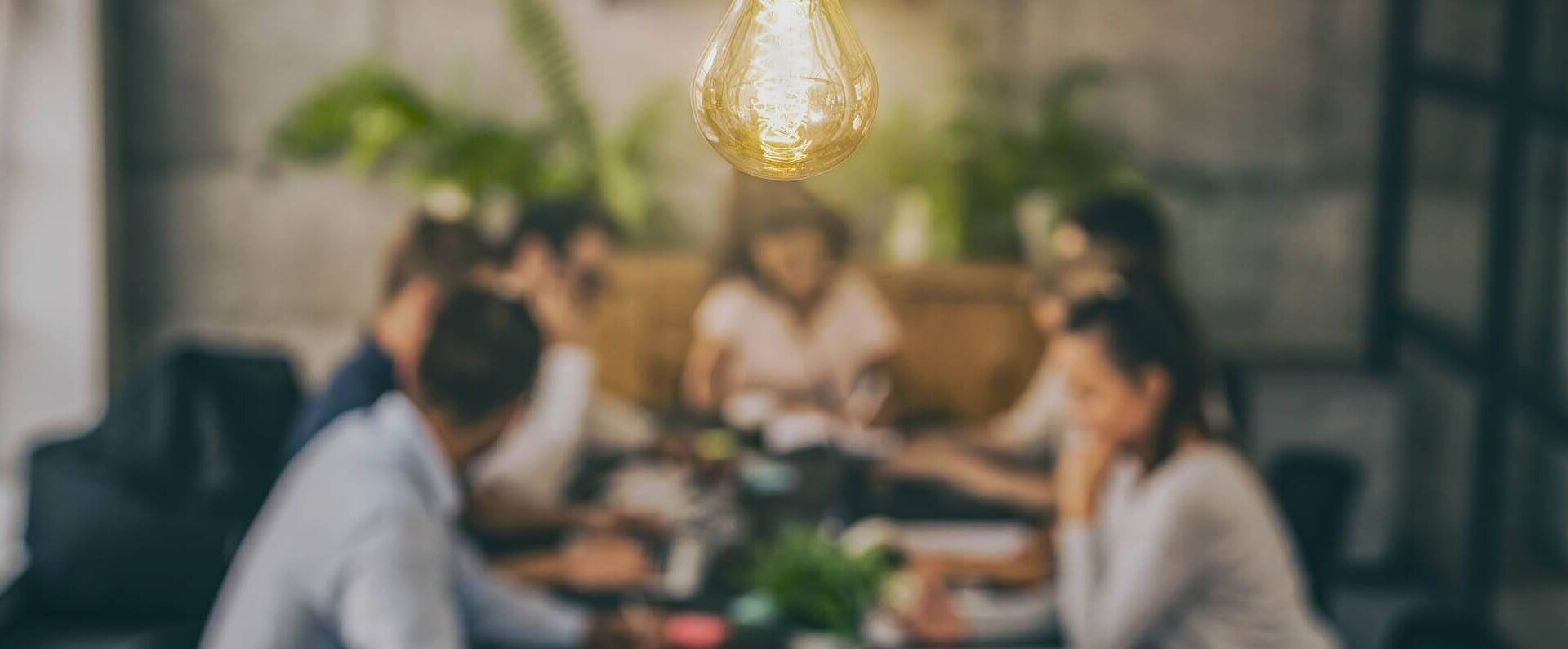 Team sat around a table with a lightbulb in focus