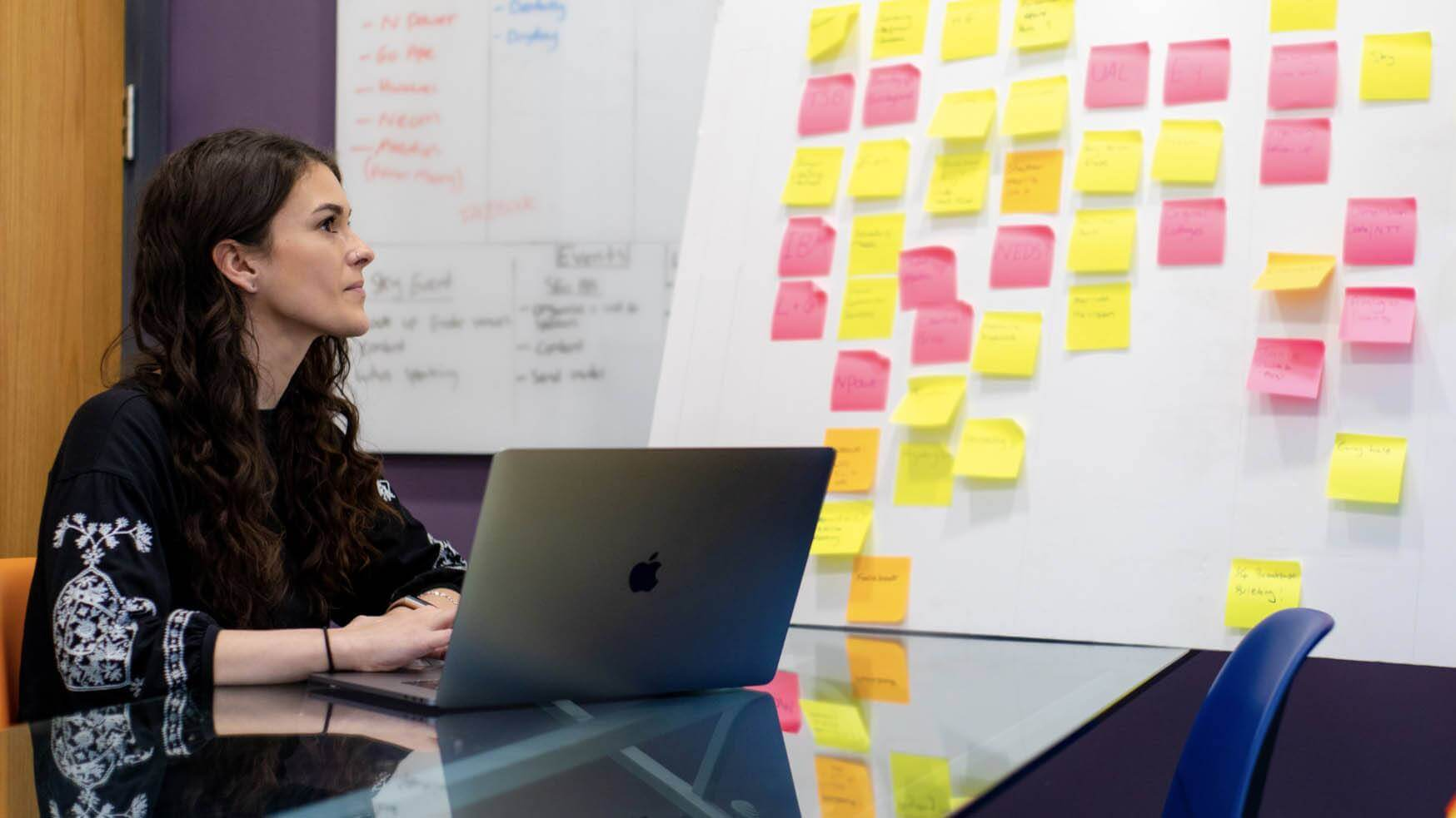 Agency worker on laptop with post-it-notes
